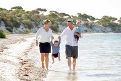 Young happy beautiful family walking together on the beach enjoying summer holidays Stock Image