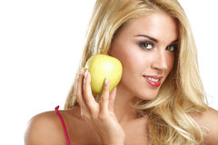 Young happy beautiful girl eating a green apple Stock Photography