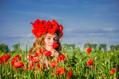 A young, happy, beautiful girl is having fun and dancing with joy in the field of flowering poppies with a wreath of poppy flowers Royalty Free Stock Photos