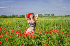 A young, happy, beautiful girl is having fun and dancing with joy in the field of flowering poppies with a wreath of poppy flowers Stock Images