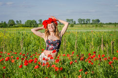 A young, happy, beautiful girl is having fun and dancing with joy in the field of flowering poppies with a wreath of poppy flowers Royalty Free Stock Photo