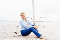 Young, happy, beautiful girl sitting on a deck of a yacht. Trave Stock Photography