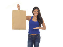 Young happy and beautiful hispanic woman holding brown shopping bag smiling excited isolated on white Royalty Free Stock Image