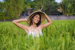 Young happy and beautiful hispanic woman playing with traditional Asian farmer hat smiling having fun posing sexy isolated on. Green rice field in Asia tourist stock image