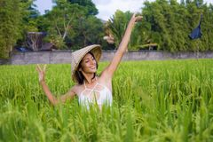 Young happy and beautiful latin woman playing with traditional Asian farmer hat smiling having fun posing sexy isolated on green. Rice field in Asia tourist stock photo