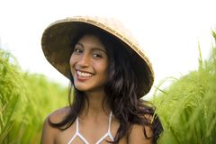 Young happy and beautiful latin woman playing with traditional Asian farmer hat smiling having fun posing sexy isolated on green. Rice field in Asia tourist stock image