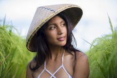 Young happy and beautiful latin woman playing with traditional Asian farmer hat smiling having fun posing sexy isolated on green. Rice field in Asia tourist stock photography