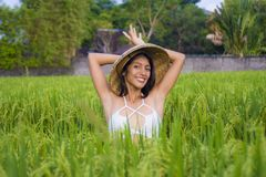 Young happy and beautiful latin woman playing with traditional Asian farmer hat smiling having fun posing sexy isolated on green. Rice field in Asia tourist stock photos
