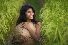 Young happy and beautiful latin woman playing with traditional Asian farmer hat smiling having fun posing sexy isolated on green. Rice field in Asia tourist stock images
