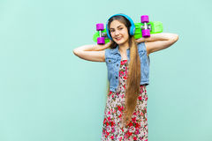 The young happy beautiful long haired blonde girl in dress and headphones, having fun with green plastic penny skateboard in front Royalty Free Stock Images