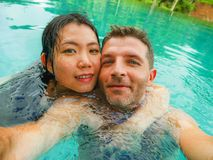 Young happy and beautiful mixed ethnicity couple Asian woman and Caucasian man taking romantic selfie picture at tropical resort royalty free stock image