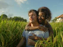 Young happy and beautiful mixed ethnicity couple with black African American woman and attractive Caucasian man cuddling and. Young happy and beautiful mixed stock images