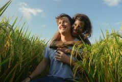 Young happy and beautiful mixed ethnicity couple with black African American woman and attractive Caucasian man cuddling and. Young happy and beautiful mixed royalty free stock images