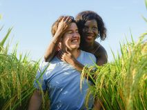 Young happy and beautiful mixed ethnicity couple with black African American woman and attractive Caucasian man cuddling and. Young happy and beautiful mixed stock photo