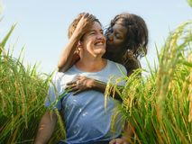 Young happy and beautiful mixed ethnicity couple with black afro American woman and attractive Caucasian man cuddling and having. Young happy and beautiful mixed stock photography