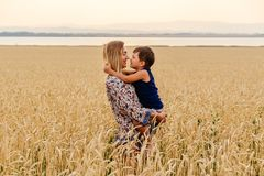Young happy beautiful mother with baby faces in wheat field royalty free stock image