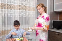 Young happy beautiful mother and her child eating Stock Images