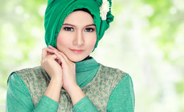 Young happy beautiful muslim woman with green costume wearing hi Royalty Free Stock Images