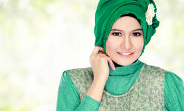 Young happy beautiful muslim woman with green costume wearing hi Royalty Free Stock Photography