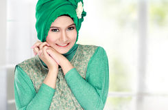 Young happy beautiful muslim woman with green costume wearing hi Royalty Free Stock Photos