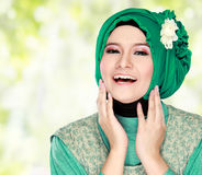 Young happy beautiful muslim woman with green costume wearing hi Stock Image