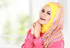 Young happy beautiful muslim woman with green costume wearing hi Royalty Free Stock Image