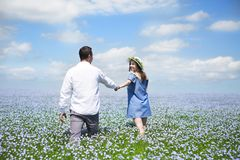 Young happy beautiful pregnant couple in linen field Stock Photos