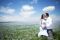 Young happy beautiful pregnant couple in linen field Stock Photo
