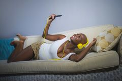 Young happy and beautiful relaxed black afro American woman listening to music with headphones and mobile phone at home sofa couch royalty free stock photography