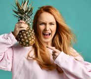 Young happy beautiful sexy woman posing laughing with pineapple fruit Royalty Free Stock Image