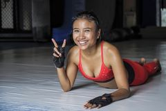 Young happy and beautiful sweaty Asian woman in sport clothes stretching on gym dojo hy sporty lifestyle concept giving peace sign Royalty Free Stock Images