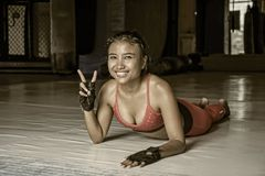 Young happy and beautiful sweaty Asian woman in sport clothes stretching on gym dojo hy sporty lifestyle concept giving peace sign Royalty Free Stock Photos