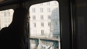 Young happy beautiful tourist woman in metro train at Paris looking at city buildings through the window slow motion.