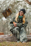 Young happy beautiful woman in camouflage outfit with barbecue grill fish sitting on forest log. Travel lifestyle concept. Stock Photo