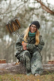 Young happy beautiful woman in camouflage outfit with barbecue grill fish sitting on forest log. Travel lifestyle concept. Royalty Free Stock Photography
