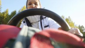 Young happy beautiful woman driving ATV through the sun, hands hold steering wheel in slow motion. 1920x1080 stock footage