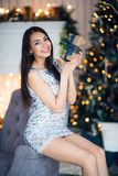 Young happy beautiful woman with gift boxes sits near Christmas tree in the room of the house.  Royalty Free Stock Images