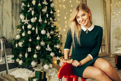 Young happy beautiful woman with gift boxes sits near Christmas tree in the room of the house. Merry Christmas and New Year.Christmas interior Stock Photo