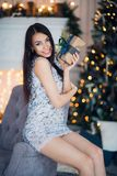 Young happy beautiful woman with gift boxes sits near Christmas tree in the room of the house.  Stock Images