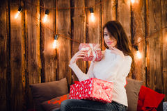 Young happy beautiful woman with gift boxes sits near wall decorated for Christmas in the room of the house. Merry xmas. And New Year Royalty Free Stock Images