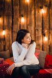 Young happy beautiful woman with gift boxes sits near wall decorated for Christmas in the room of the house. Merry xmas. And New Year Royalty Free Stock Photo
