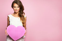 Young happy beautiful woman hold Love symbol red heart. Isolated on studio pink background female model Stock Photography