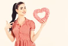 Young happy beautiful woman hold Love symbol. Pink heart. Isolated on white background female model stock photo