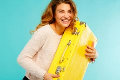 Young happy woman holding yellow suitcase over blue background. Young happy beautiful woman holding yellow suitcase over blue background Royalty Free Stock Images
