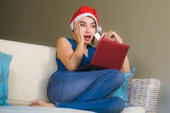 Young happy and beautiful woman relaxed at home couch in Santa hat using laptop computer paying for Christmas present with credit royalty free stock image