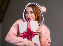 Young happy and beautiful woman in winter warm hoodie holding Christmas or birthday present box with ribbon in her hands smiling c royalty free stock photography