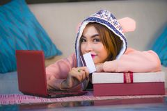 Young happy and beautiful woman in winter warm hoodie holding Christmas or birthday present box with ribbon in her hands smiling c. Young happy and beautiful royalty free stock image