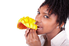 Young happy black / african american woman eating fresh mango Stock Photography