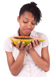 Young happy black / african american woman holding fresh papaya Royalty Free Stock Photos