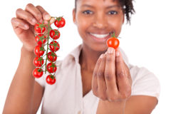 Young happy black / african american woman holding tomatoes Stock Photography